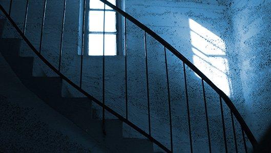 Symbolbild: dunkles Treppenhaus mit einem Fenster, durch das die Sonne rein scheint.