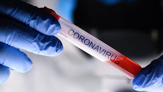 Informationen zum Coronavirus - Symboldbild: eine Hand mit blauem Gumminhandschuh hält ein Reagenzglas, auf dem der Schriftzug Coronavirus steht.