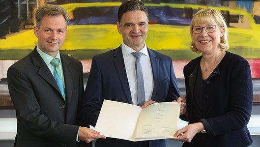 In einer Feierstunde nahmen Prof. Ursula Gather, Rektorin der TU Dortmund (r.) und Prof. Götz S. Uhrig, Dekan der Fakultät Physik (l.), die Verleihung des Ehrentitels an Dr. med. Karl-hein Bauer vor.