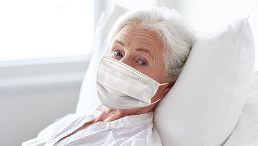 Eine alte Dame liegt im Krankenbett und trägt eine medizinische Maske.