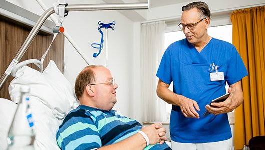 Chefarzt Dr. Ludwig im Gespräch mit einem Patienten.