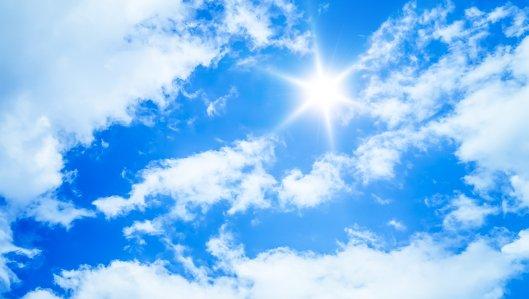 Symbolbild: blauer Himmel mit leichten Wolken und Sonne.