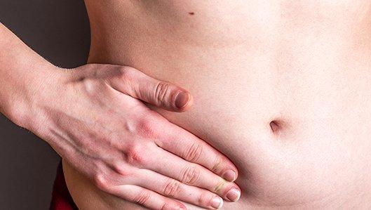 Ein Mann drückt seine Hand seitich auf den nackten Bauch.