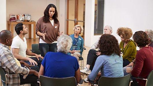 Mitglieder einer Selbsthilfegruppe sitzen im Kreis