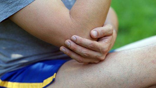 Ein Sportler umfasst seinen offenbar schmerzenden Ellenbogen