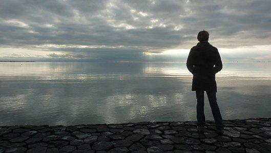 Symbolbild: Ein Mann schaut gedankenverloren auf einen See, bewölkter Abendhimmel.