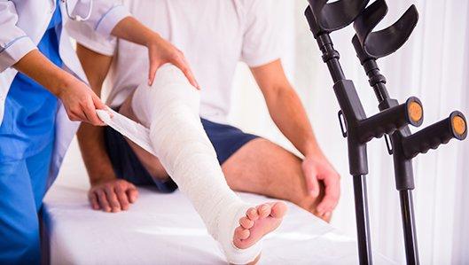 Eine Ärztin legt einem Patienten einen Beinvrband an, im Vordergrund steht ein Paar Gehhilfen