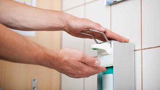 Handhygiene - Symbolbild: Zwei Hände bei der Betätigung des Desinfektionsmittel-Spenders.