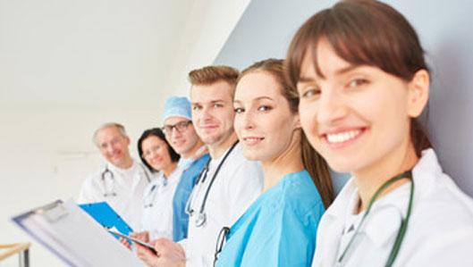 Jobs - Symbolbild - eine Reihe junger Ärztinnen und Ärzte lehnt an der Wand und lächelt in die Kamera.