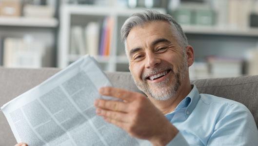 Aktuelles - Symbolbild: ein freundlicher Mann mit grauen Haaren und Bart sitzt auf einer Couch und liest Zeitung.