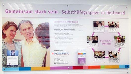 Acrylwand im Knappschaftskrankenhaus Lütgendortmund mit Informationen zu Selbsthilfeangeboten
