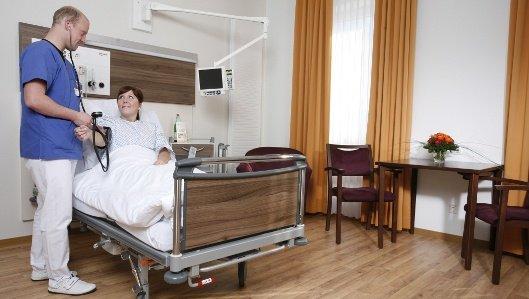 Ein Pfleger misst bei einer Patientin den Blutdruck.