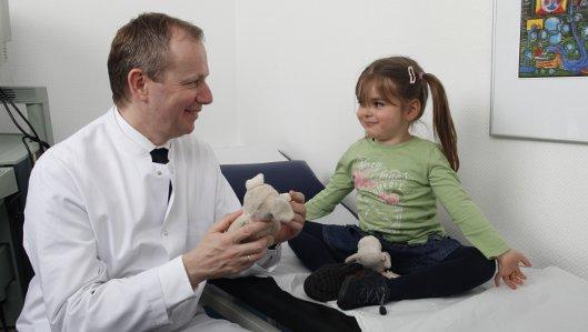Chefarzt Dr. Stefan Orth im Gespäch mit einem kleinen Mädchen
