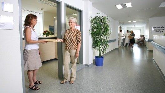 Aufnahmemitarbeiterin übergibt auf einem Krankenhausflur einer Patientin ihre Unterlagen.