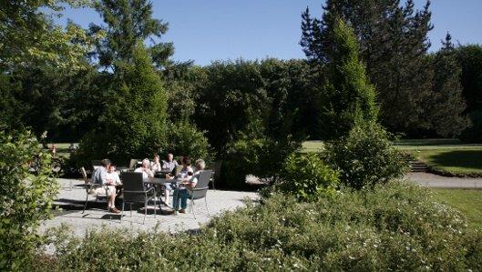 Ein Tisch mit vielen Gästen auf der Terrasse der Cafeteria im Park des Knappschaftskrankenhauses Dortmund.