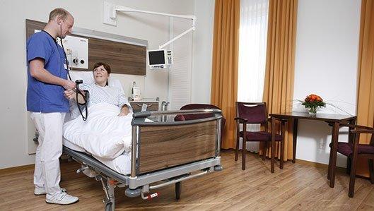 Ein Pfleger misst den Blutdruck einer Patientin.
