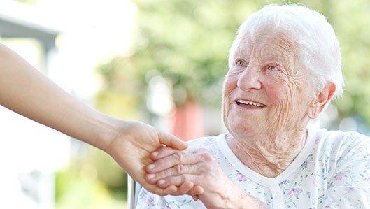 Eine ältere Dame hät mit einem Lächeln eine ihr hingehaltene Hand.