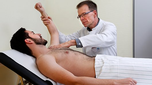 Schmerztherapie: Dr. Hofmann untersucht einen Patienten